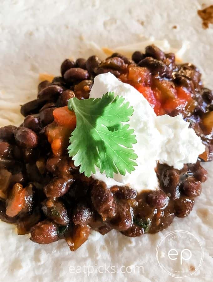 Black Beans with sour cream dollop and cilantro leaf on flour tortilla