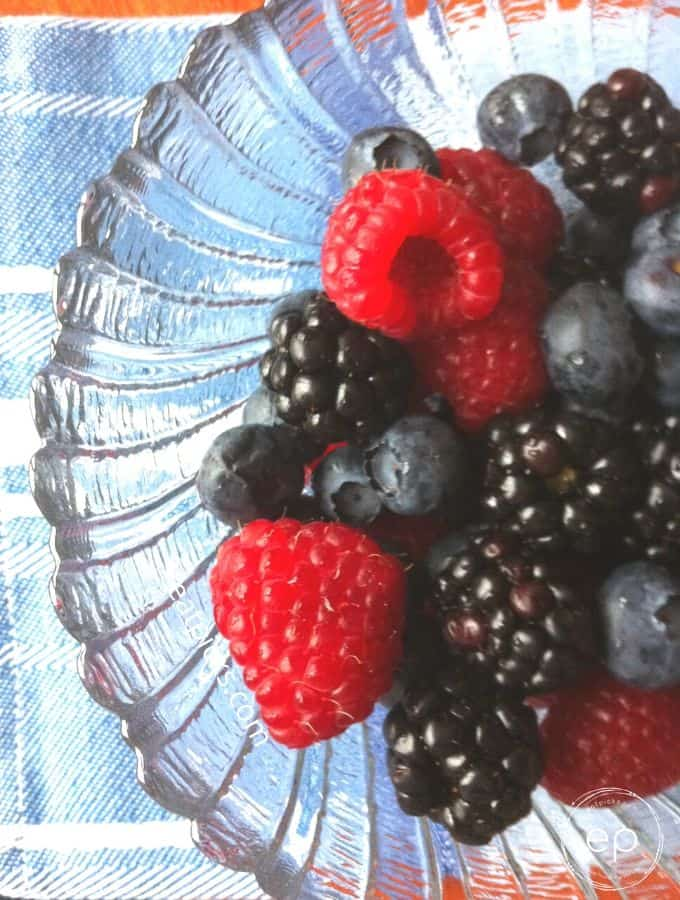 Fresh mixed raspberry, blackberry, blueberry berries in clear bowl