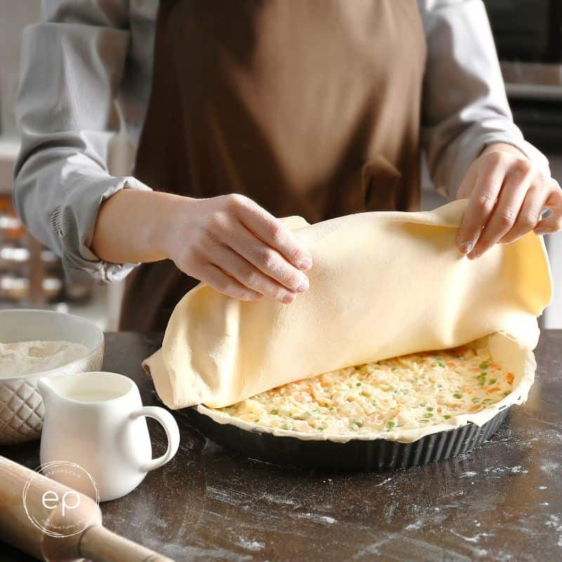 Person placing crust on top of potpie filling