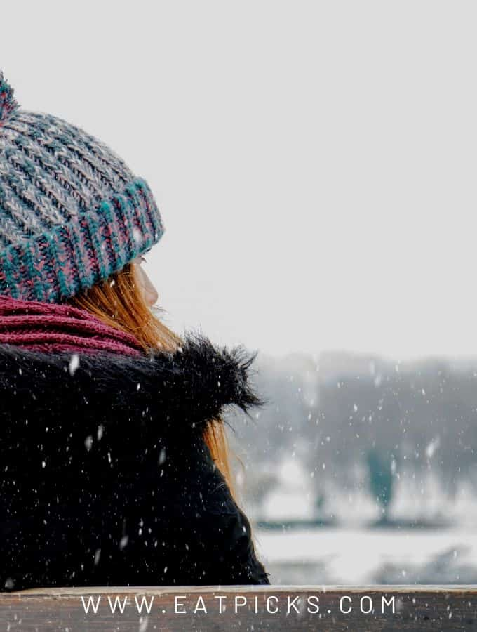 Girl in hat watching snow