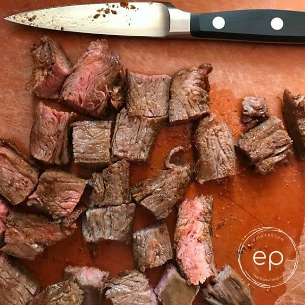 Steak slices on board with knife