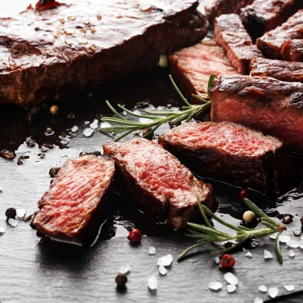 Steak slices on board with rosemary salt