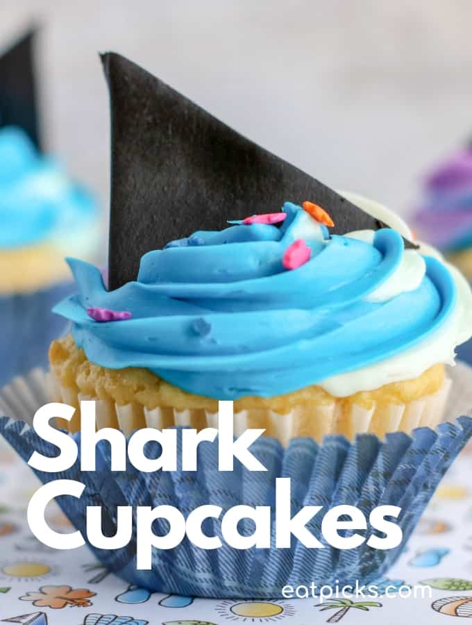 Shark Fin Cupcakes with blue and purple frosting in paper cupcake wrapper