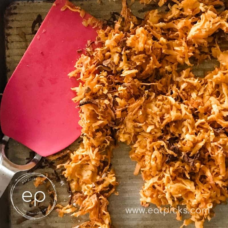 Crispy shredded sweet potatoes on pan with red spatula