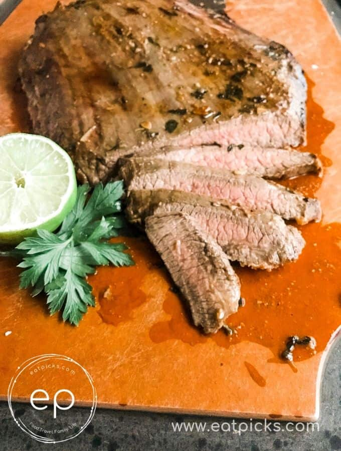 Sliced Cooked Garlic Lime Flank Steak on cutting board with